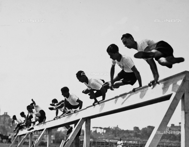 Athletes, of the Fascist Academy, portrayed while jumping a hurdle