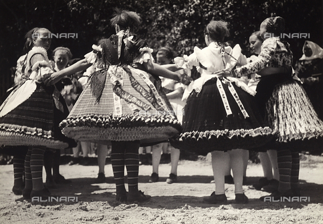 Traditional dance scene with ladies wearing Hungarian traditional dresses