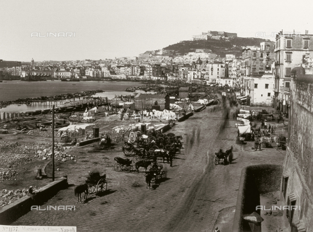 Panorama of the Gulf of Naples taken from the busy Via Marina Nuova. On the left run-down shacks built on the seashore, in the background Castel Sant'Elmo