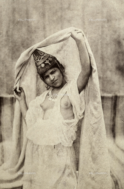 Portrait of a young Algerian lady from Orano, in traditional dress, with half-naked bust.