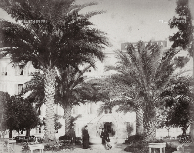 two men and lady portrayed in the Hotel Voctoria park in Sanremo.