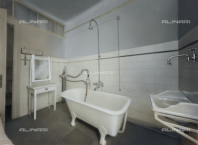 Inner view of an ambulatory of an Institute for physiotherapeutic treatment, with a bathtub, a sink and a cabinet with mirror