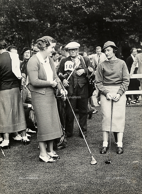 Miss Barton poses during a golf tournament, surrounded by a group of people, on the course