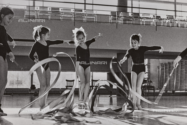 Young Russian dancers perform artistic gymnastic exercises in a Soviet gym