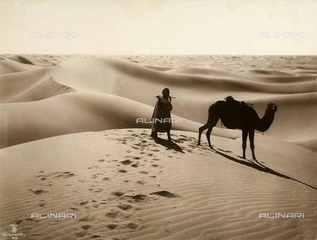 Bedouin and camel amidst the Tunisian desert dunes