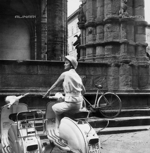 The actress Olivia de Havilland in Lambretta near to the Loggia dei Lanzi in Florence