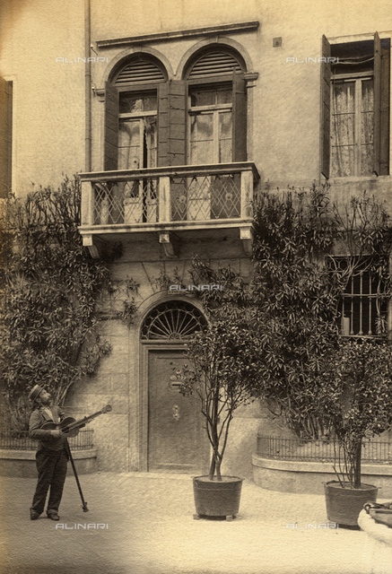1920 ca, VENEZIA, ITALY: Serenade of love, from an invalid man with crutch and guitar, in unidentified little square in Venice