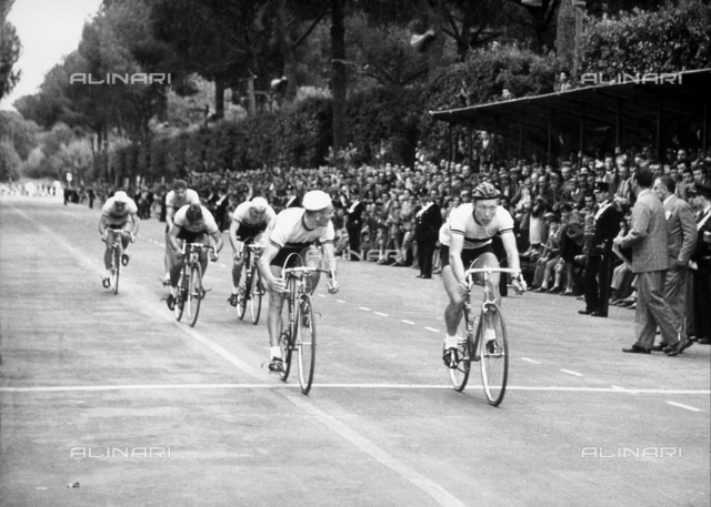 Cycling competition; on the left, several spectators