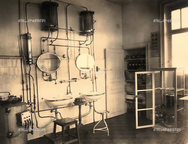 An infirmery at a mining camp with two sinks connected to pipes, and a few cabinets with medical supplies