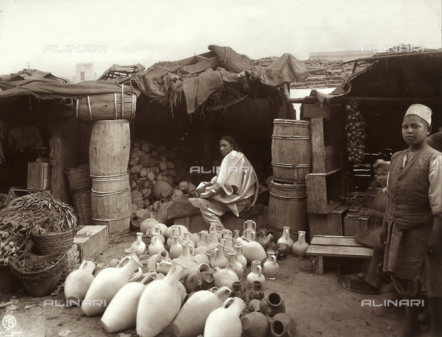 The Arab market: in the foreground there are some clay urns and pots, wooden barrels and vegetables. The image dates back to the Italian conquest of Libya, just after the Italian - Turkish war of 1911-1912
