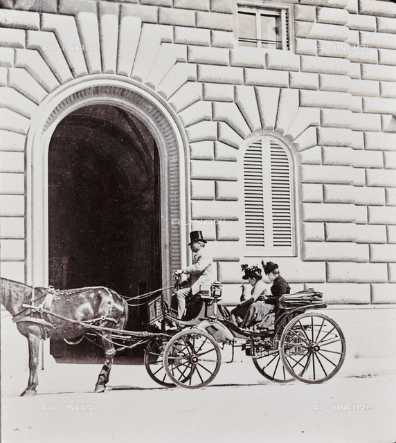 Carriage with ladies and coachman in front of the entrance of a building, Florence