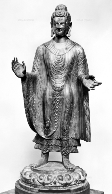 CHINA: BUDDHA. Chinese Northern Wei (386-557 A.D.) gilt bronze standing figure of Buddha standing with outstretched arms on a lotus pedestal. Height: 55.25 inches; width: 19.5 inches.