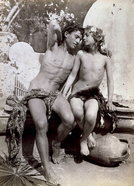 Couple of semi-nude adolescents portrayed as Dio Pan and a young Ninfa. They are sitting on a small stone wall, in atteggiamento di inequivocabile sensualità