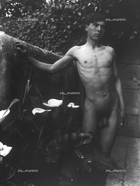 Nude youth poses next to calla lilies