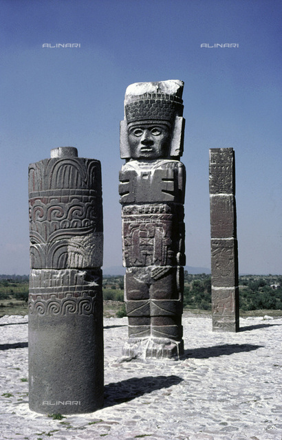Toltec Atlantid figure flanked by two carved columns, Tula, Mexico, 950-1150 AD. The statue stands on top of the Pyramid of Quetzalcoatl