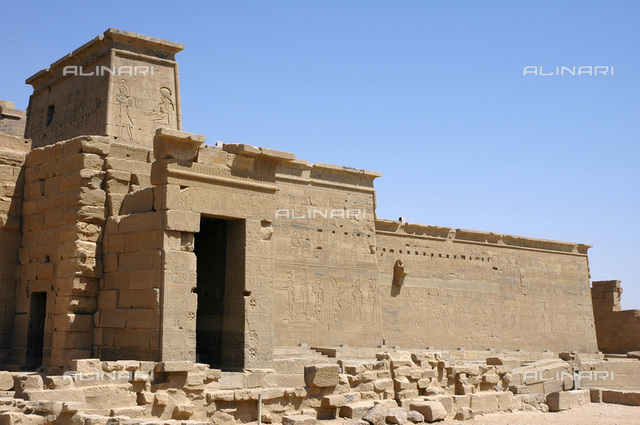 View of the side entrance to the hypostyle hall of the Temple of Isis, Philae, Egypt. To the left and right of the entrance are Christian crosses made by Copts who re-used the building for Christian worship after 550 AD. The construction of the temple dedicated to the Ancient Egyptian goddess Isis on the island of Philae started during the reign of Ptolemy II Philadelphus in the 3rd century BC and was completed by his successor Ptolemy III Euergetes. It was the last remaining outpost of the Ancient Egyptian religion when the Eastern Roman Emperor Justinian closed it down in c550. After damage caused by flooding after the construction of the Aswan Dam, the temple complex was moved, piece by piece, to the nearby island of Agilkai in 1977-1980