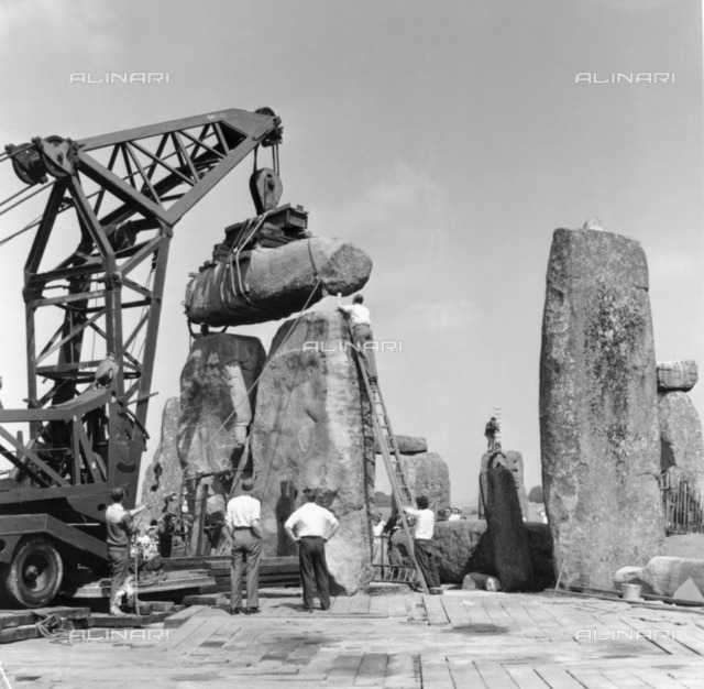 Re-erection of Trilithon lintel, Stonehenge, Wiltshire, 1958. Re-erection of Trilithon lintel 158 by the 60 ton 'Brabazon Crane', the larger of two cranes used to lift stones. The lintel is being lowered and man-handled into its final resting position on upright stones 57 and 58. Photographed by R J C Atkinson, January 1958