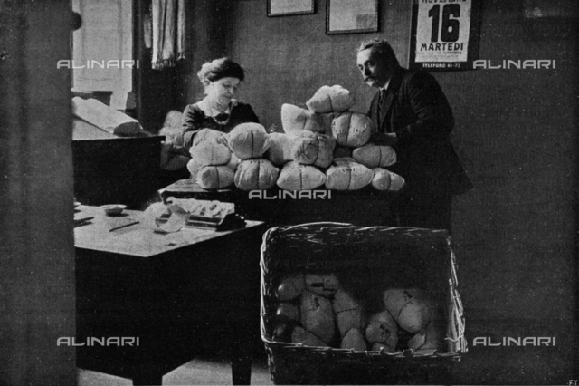 """Civil mobilization during the First World War: the packaging of the parcel of the soldier by the Committee of Porta Genova in Milan. Photography taken from the magazine """"L 'Illustration Italian"""" of December 12, 1915, n. 50, page 499"""
