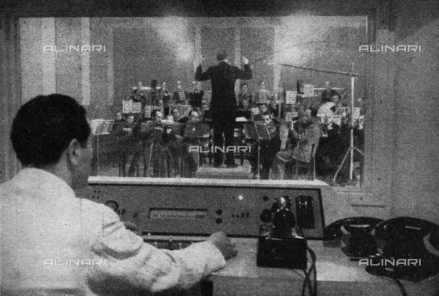 """L'orchestra Spaggiari durante uno dei suoi programmi radio: il tecnico dei suoni regola la trasmissione, fotografia tratta dalla rivista """"L'Illustrazione Italiana"""" del 26 marzo 1943, pagina 230"""
