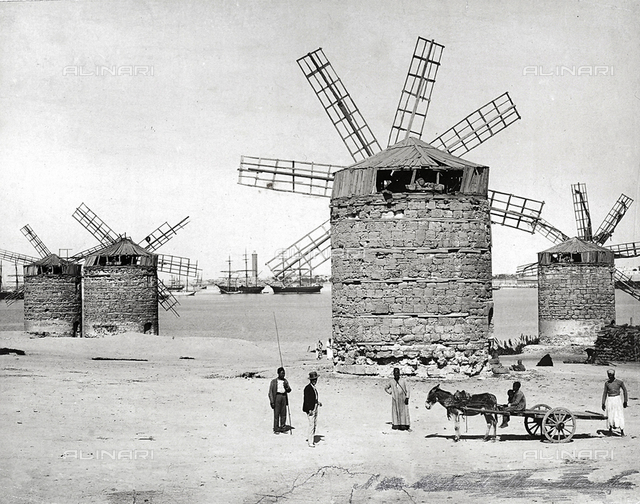 Windmills on the Mediterranean Sea in Alexandria, Egypt. In front, some egyptians posing with a small cart