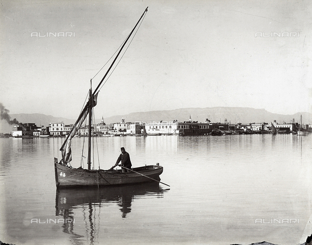 Panoramic view of a town on the Suez Canal, in Egypt. A man is photographed on board a boat