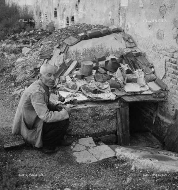 A scene of social emargination in the outskirts of Milan. In the foreground, a man is crouching in front af a wretched makeshift shelter set against a wall