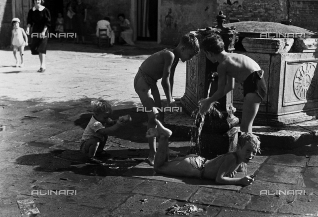 """Boys at the fountain in Summertime"". Four boys play in the water, near a fountain and a well; in the background, a few women and girls are working near the entrance to their homes"