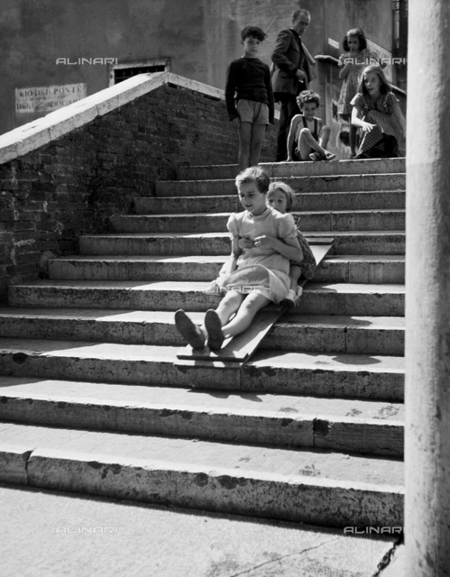 "St. Barnaba, Venice; Children, slide on the Beccarie Bridge"". A group of children play on the bridge, sliding down the step on a piece of wood"