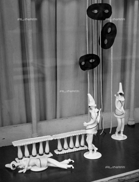 Statuettes in biscuit of a small group of Punchinello in various positions. The refined objects are set out on a dark colored shelf, suggesting a miniature stage. A few black masks are hanging above, which completes the Carnival atmosphere