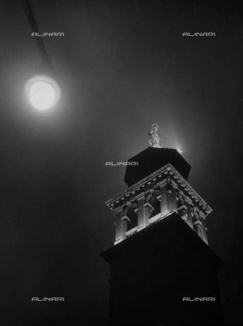 """The Virgin of Carmelo!"" Night view of the belltower of the Carmini, or rather the Church of St. Mary of Carmelo, in Venice. The building is illuminated for a religious ceremony. A statue of the Madonna del Carmelo stands at the top of the belltower"