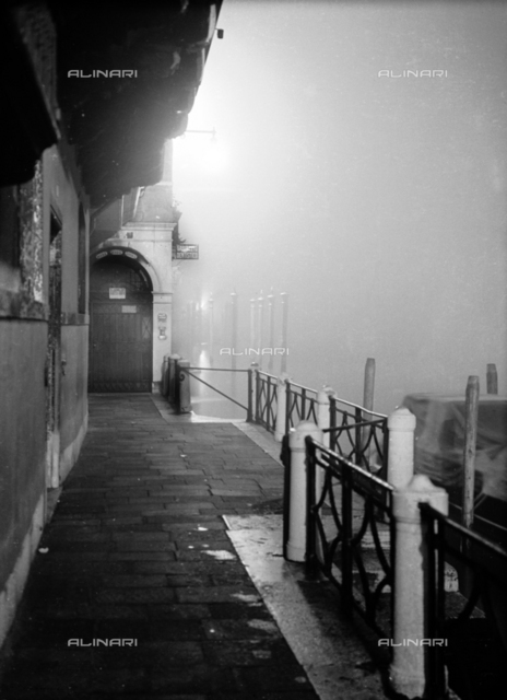 Nocturnal, street-level view of a building in Venice, deserted and shrouded by the evening fog