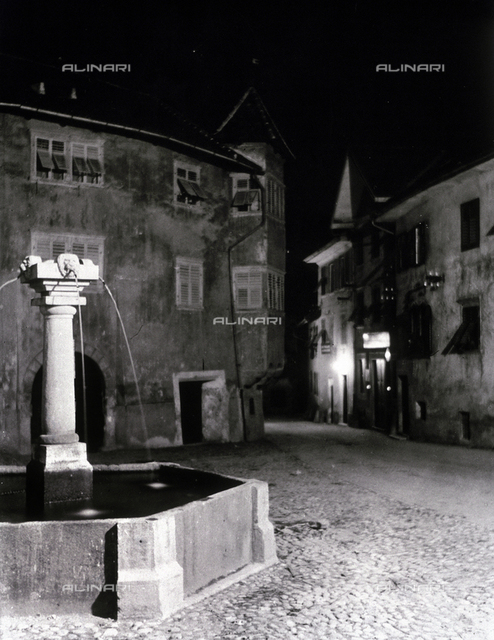 Night view of a square in Caldaro. In the foreground, a polygonal shaped fountain