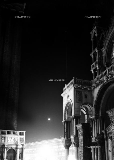 Eclipse of the moon photographed on a limpid Venetian night. In the foreground, a view of the end part of the right facade of the Basilica of San Marco