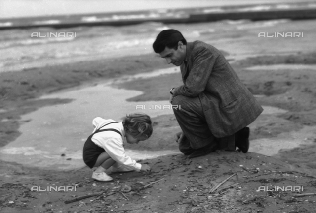 Girl gathering shells with her father, Lido of Venice