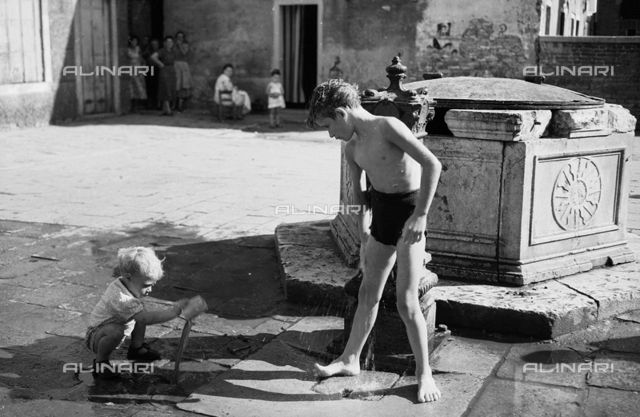 Children playing with the water from a fountain in Venice