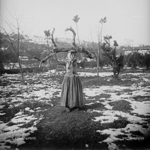 Portrait of woman carrying a tree trunk
