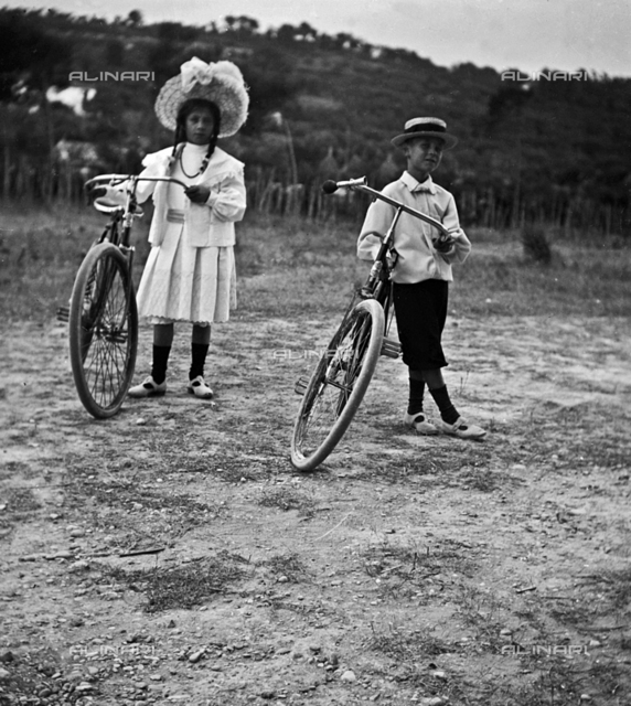 Portrait of two children with their bicycles