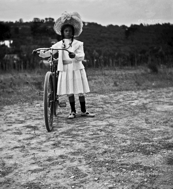 Portrait of a girl with her bicycle on a country road