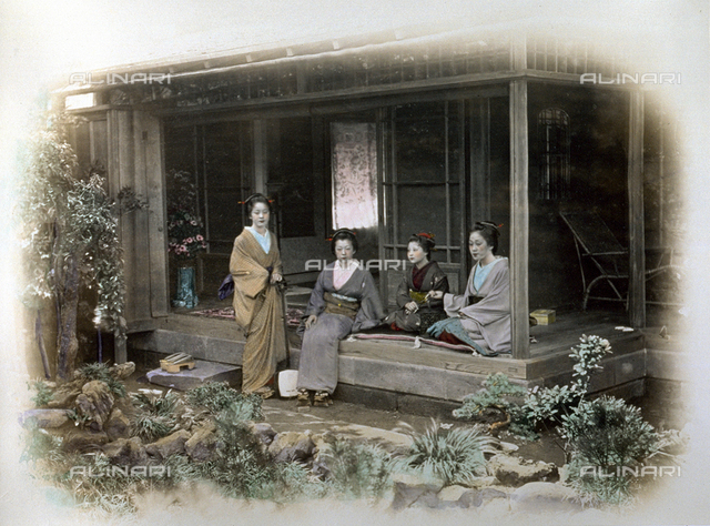 Full-length portrait of four young geishas in traditional dress. Three of them are seated under the portico of a tea house while the fourth, standing, has a shyamisen on her left arm