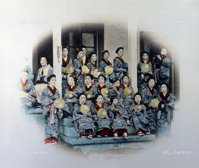 Portrait of a group of young japanese dancers. They are wearing traditional clothes in the same fabric, and are holding small fans. A few of them are playing the transverse flute