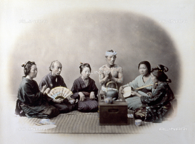 Portrait of a group of japanese sitting in a semi-circle on the ground. They are wearing traditional clothes. On the right a woman plays the shyamisen; beside her there is a bare-chested man, completely covered in tatoos. In the foreground a stove, on which a kettle and a tea pot are placed. On the left, a man with a fan in his hand