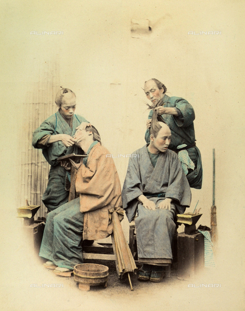 Two young japanese in a barber's having their face and head shaved. The four people are wearing traditional clothes. On the floot there is an umbrella and a bucket