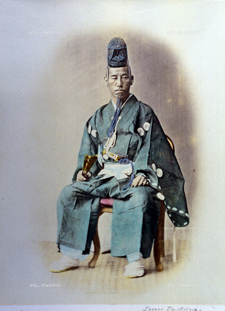 Full-length portrait of a japanese prince. He is seated, wearing magnificent tradtional dress, holding a fan and with a special kind of cap on his head