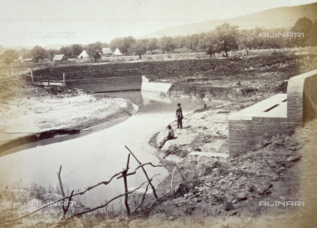 Agricultural landscape. In the foreground an artificial canal. On the banks of the river two men