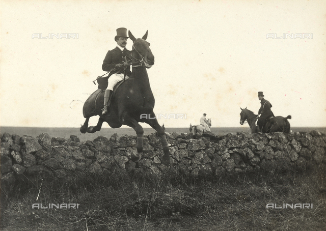 Man on horseback jumping a short wall in the Roman countryside