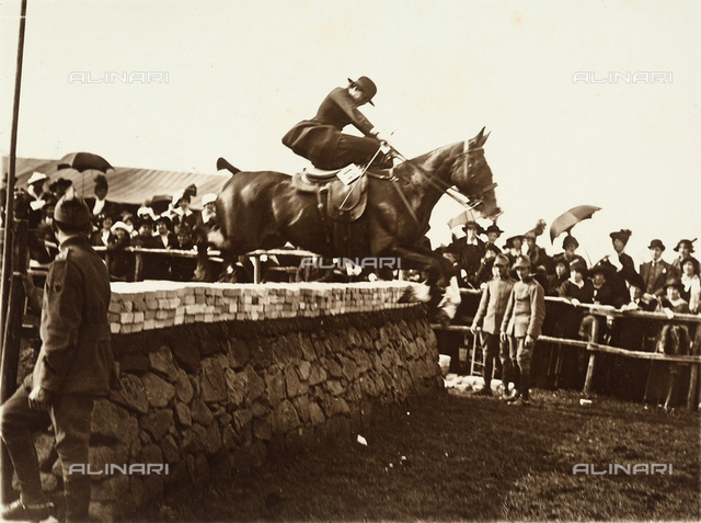 Woman on horseback jumping over an obstacle in the Roman countryside
