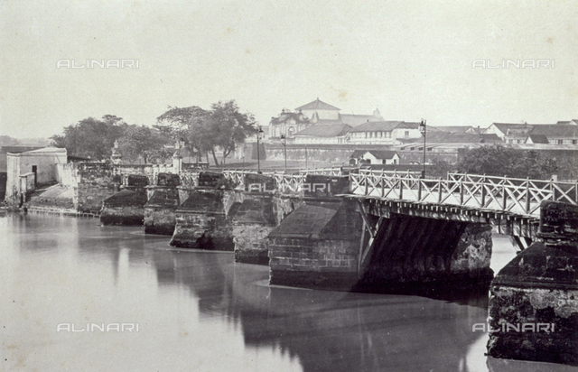 The Large Bridge built over the Pasig river in Manila. In the background the Church of Saint Francis surrounded by other buildings