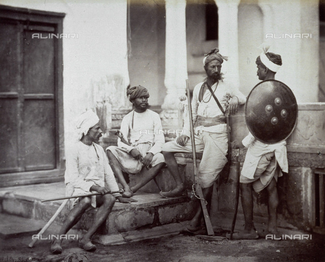 Portrait of a group of indian warriors. They are furnished with rifles and one of them has a shield