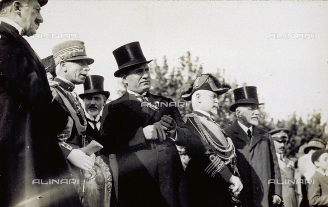 Portrait of Benito Mussolini and a group of men in elegant day dress. To the left of the Duce is Admiral Thaon di Revel in dress uniform. Mussolini wears a top hat and gloves