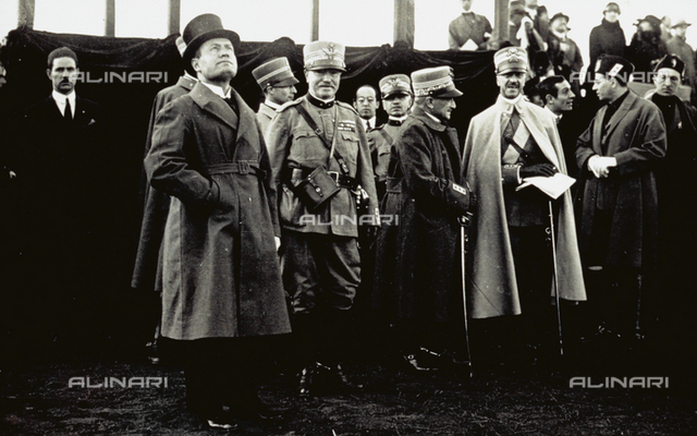 Full-length portrait of Benito Mussolini. On his left a few officers in dress uniform, including Marshal Diaz